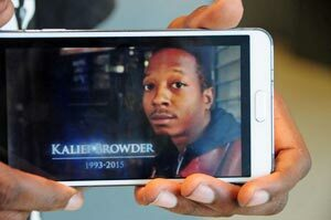 Kamal Browder holding his phone with an image of his late brother, Kalief Browder.